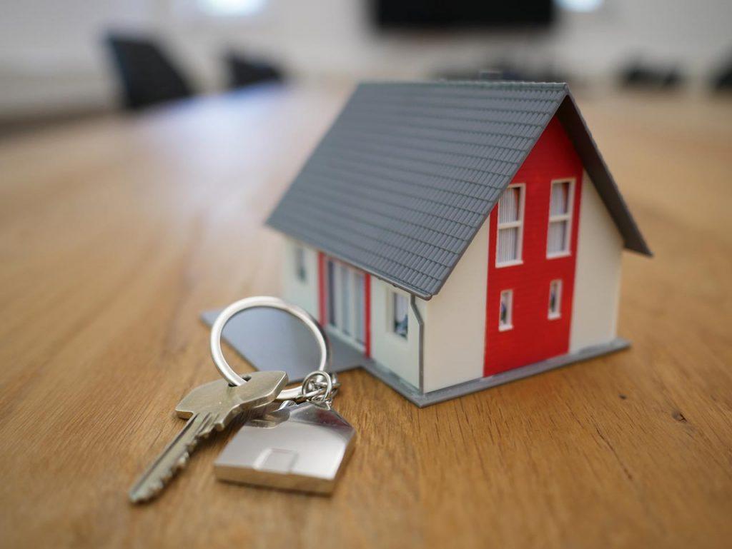 Una maqueta de una casa junto a una llave