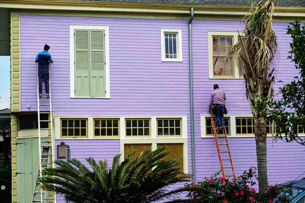 Dos hombres haciendo una reforma en una casa, pintando las paredes exteriores